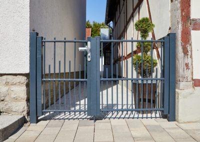 Graues Eingangstor aus Metall mit Türgriff