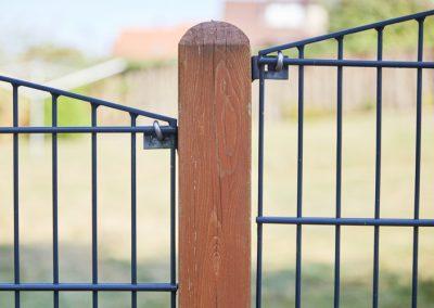 Stabiler Metallzaun in Kombination mit Pfosten aus Holz