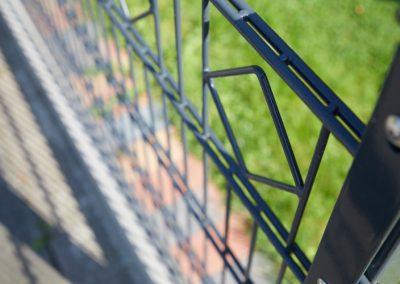 Grauer Metallzaun mit moderner Musterung